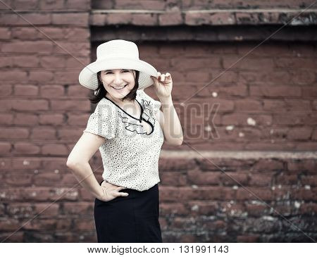 Smiling woman in white hat posing against brick wall background. Selective focus on woman. Toned photo with copy space. Vintage style photo.