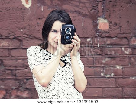 Pretty young woman with vintage camera against brick wall background. Girl taking photo outdoor. Selective focus on model. Retro style photo. Toned photo with copy space. Vintage style photo.