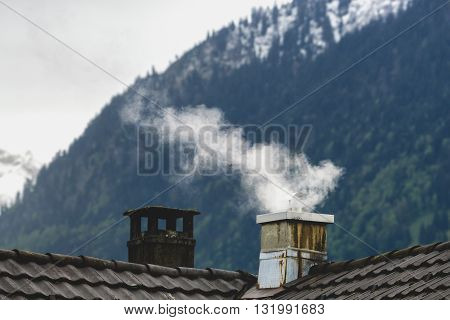 Smoke raising from chimney in the air with mountain background in winter