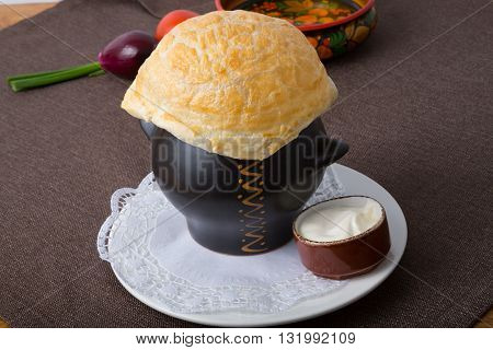 Russian soup pot with baked bread over it