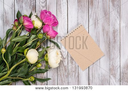 Notebook and bouquet of peonies flowers on the wooden background. Place for text. Top view.