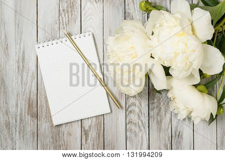 White peonies flowers with notebook and pencil on the white painted wooden planks. Place for text. Top view.