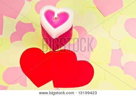 A Heart Shaped Candle Over Cute Paper Hearts