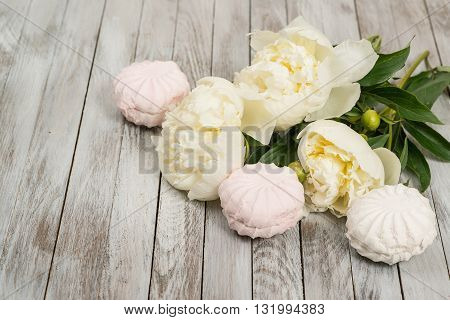 Beautiful white peonies flowers and marshmallows on the white wooden background.