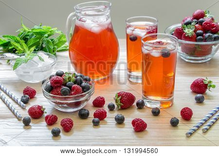 2 compotes of raspberries strawberries blueberries near 2 bowls with berries bowl of ice mint leaves carafe compote straws on light background scattered berries. Berries compote. Horizontal.