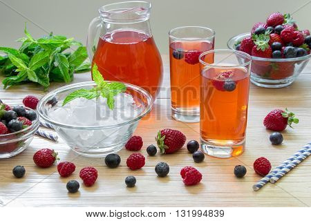 2 compotes of raspberries strawberries blueberries near bowl of ice 2 bowls with berries mint leaves carafe compote straws on light background scattered berries. Berries compote. Horizontal.