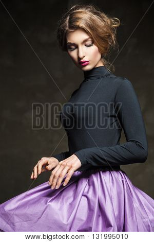 Portrait of fair-haired model with pink lips sitting in studio and looking away.
