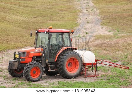 EARLTOWN CANADA - MAY 26 2016: Kubota tractor parked in agricultural outdoor setting. Kubota Corporation is a Japanese heavy equipment manufacturer with an array of products such as tractors and agricultural equipment.