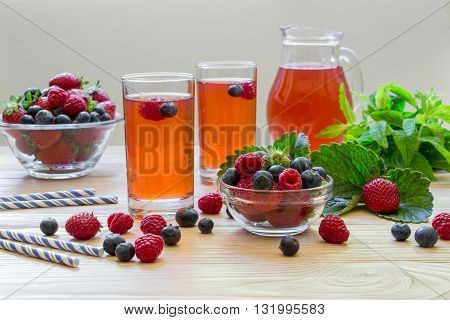 Two glasses of compote raspberries strawberries blueberries near bowls with berries right carafe compote mint leaves on ight wood background scattered berries. Fresh berries compote. Horizontal.