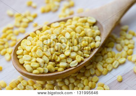 close up yellow millet on wooden spoon