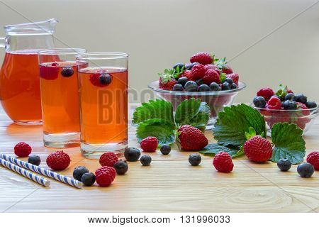 Left two glasses of berries compote near 2 bowls with berries carafe compote on a light wooden background scattered berries and some empty space. Fresh berries compote and empty space. Horizontal.