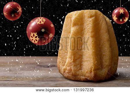 pandoro cake on wood with christmas balls and snowflake