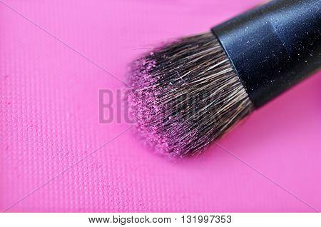 Make-up brush on pink crushed blush background