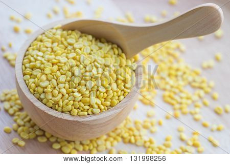 close up yellow millet grains in wooden bowl