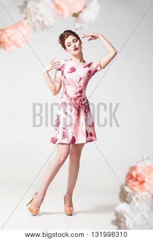 Studio shot of beautiful woman with make-up in floral dress.