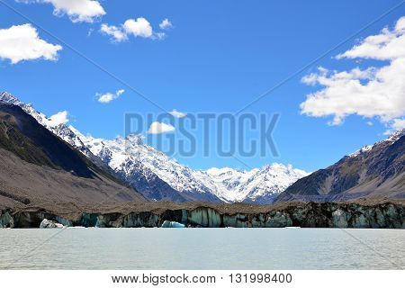 Glacier on a lake at the foot of snow covered mountains