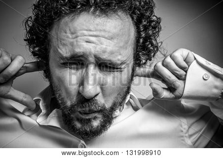 I do not want to hear anything, man with intense expression, white shirt