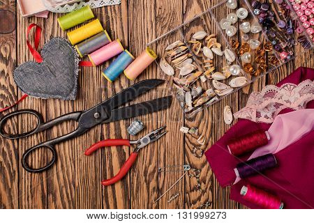 Set for needlework placed on wooden background materials and tools.Top view.