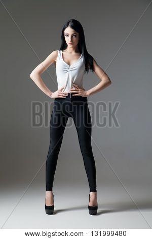 Portrait of beautiful dark-haired model on high heels posing in studio
