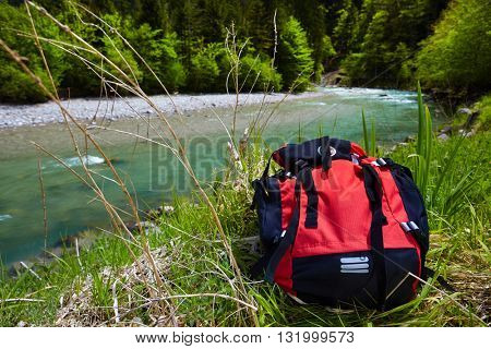 backpack over alpine stream. Tourist concept
