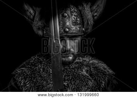 Warning, Viking warrior with a huge sword and helmet with horns
