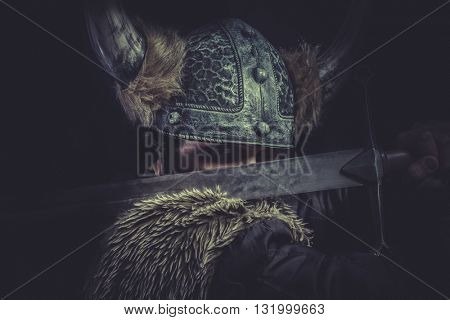 Furious, Viking warrior with a huge sword and helmet with horns