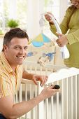 image of pregnant woman  - Portrait of man fixing baby bed - JPG