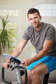 foto of exercise bike  - Man training on exercise bike at home - JPG