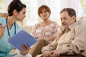 stock photo of health-care  - Nurse talking with elderly people showing test results during routine examination at home - JPG