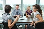 stock photo of business meetings  - Group of young business people talking on business meeting at office - JPG