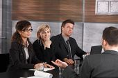 Panel of friendly businesspeople sitting at meeting table conducting job interview listening to appl