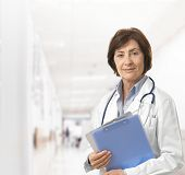 Portrait of senior female doctor on hospital corridor holding clipboard looking at camera smiling.?