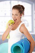 Постер, плакат: Красивая девушка кусать яблоко после занятий в тренажерном зале