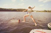 Kids jumping off a boat into the lake. Vintage Instagram effect. Some motion blur poster