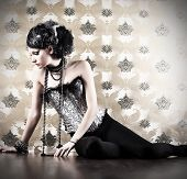 Beautiful fashionable woman over vintage background.