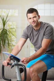 picture of exercise bike  - Man training on exercise bike at home - JPG