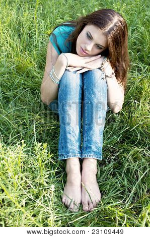 A beautiful girl sitting on grass