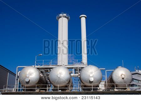 Silver tanks with smokestacks