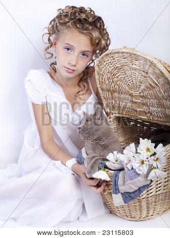 Eine Mädchen mit lockiges Haar spielt mit einer Katze im Korb
