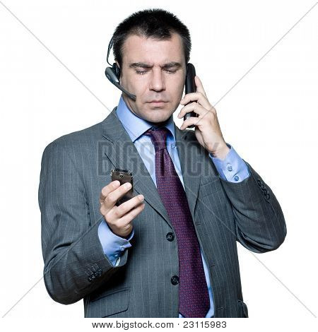 Portrait of businessman wearing headset and using mobile phone busy with multiple telephone in studio isolated white background