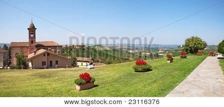 Panoramic view on green lawn, old church and hills of Piedmont in northern Italy.