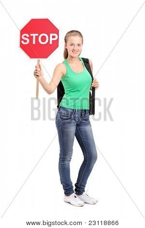 Full length portrait of a young woman holding a traffic sign stop isolated on white background