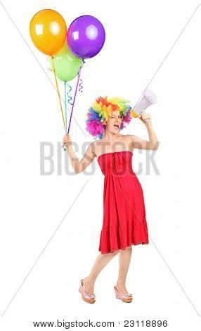 Full length portrait of a woman yelling via a loudspeaker and holding balloons isolated on white background