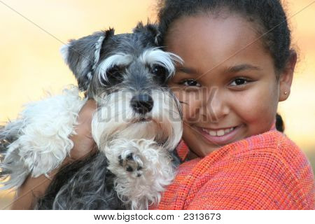 Little Girl And Her Miniature Schnauzer Puppy.