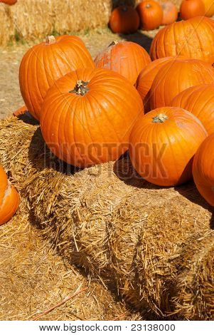 Bright Orange Pumpkins Stacked On Hay Bales