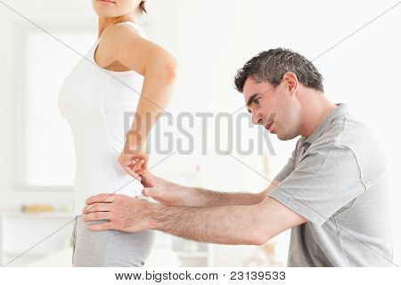 Chiropractor Examining A Woman's Back