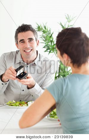 Smiling Man Proposing To His Surprised Girlfriend During Dinner