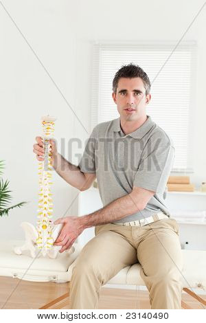 Chiropractor Holding The Model-spine Looking Into The Camera