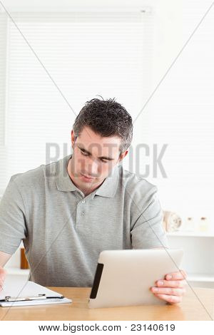 Doctor Sitting At A Table With A Tablet And A Chart