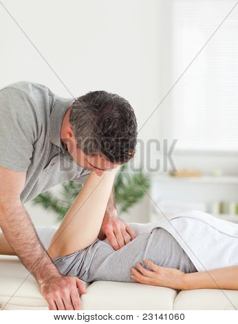 A Chiropractor Stretches Woman's Leg